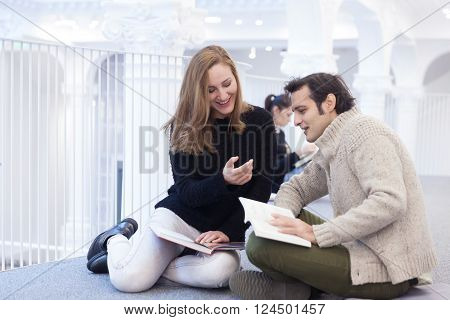 Young couple ignoring the environment being addicted to social media. Conceptual image with people pretending that are always using phones or tablets in normal life.