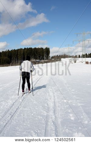 A senior man is doing cross-country skiing