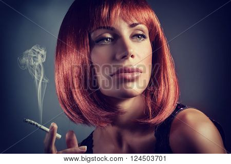 Fashion portrait of gorgeous redhead woman smoking in the studio over dark background, female with beautiful hairstyle and sensual look