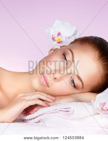 Closeup portrait of a beautiful woman, face with no makeup and perfect clear skin, female with a white orchid flower, lying down on massage table, enjoying a relaxing day at spa, pink background