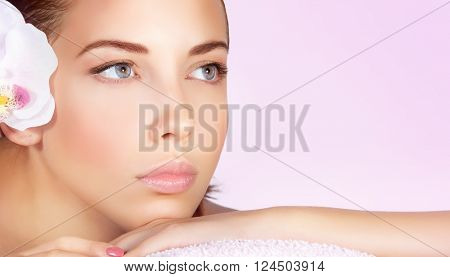 Closeup portrait of a beautiful woman, perfect face with no makeup makeup, female lying down on massage table white orchid flower in hair, enjoying day spa, shot over pink background with copy space