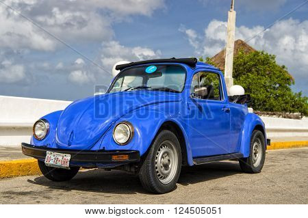 Cozumel Mexico - December 24 2015: Blue retro small car standing with no people on ground sunny day outdoor