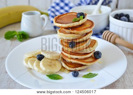 Pancakes for breakfast with honey and blueberries