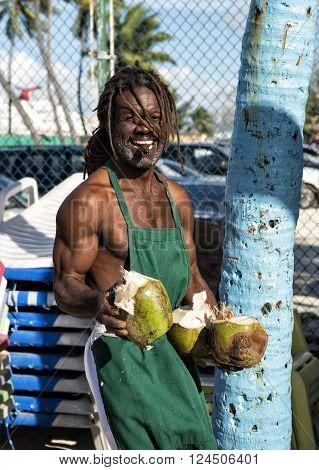 Nassau, Bahamas - January 07 2016: afroamerican  muscular man holding broken big raw coconut smiling and smoking cigar sunny day outdoor