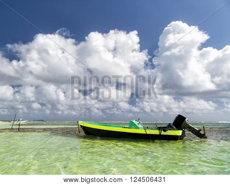 Bright motor boat on clean water on beautiful marine beach of Antigua St. Johns with cloudy sky outdoor on natural background