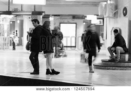 Young couple ignoring the environment being addicted to social media. Conceptual image with people pretending that are always using phones or tablets in normal life. ** Note: Visible grain at 100%, best at smaller sizes