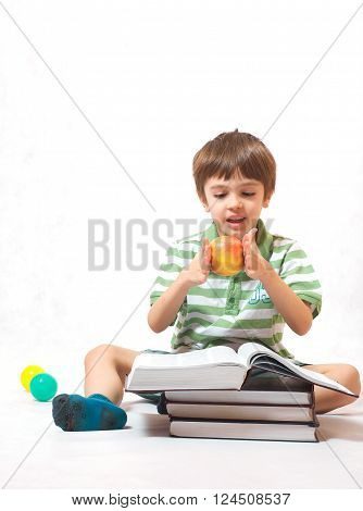 A Boy With An Apple And A Pile Of Books