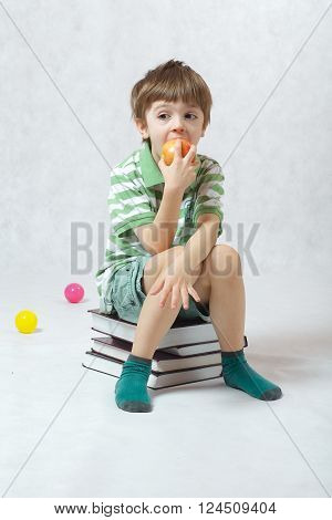 A Boy Eating An Apple Sitting On A Pile Of Books