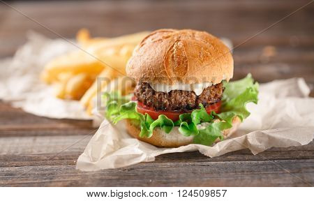 Homemade burger with french fries on wooden table