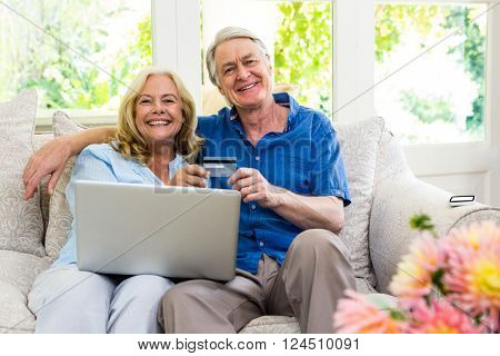 Portrait of happy senior couple holding smart card with laptop while sitting at home