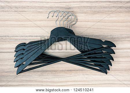 Set of black coat hangers on the wooden background.