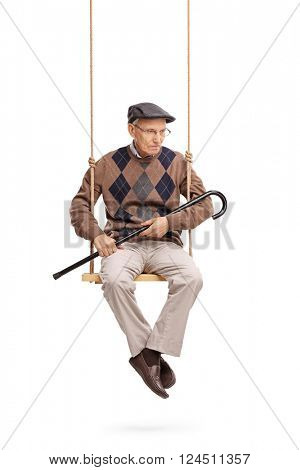 Vertical shot of a depressed senior man looking down seated on a wooden swing isolated on white background