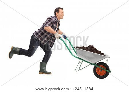 Young gardener pushing a wheelbarrow full of dirt and running isolated on white background