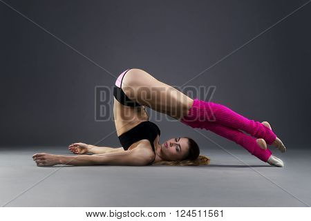 Muscular attractive fitness woman warming up in the studio on gray background. Flexible dancer