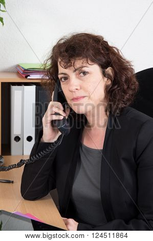 Mid Age Businesswoman On Phone At Desk