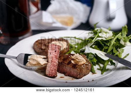 Medium-rare beef filet grilled with fresh arugula salad leaves on white plate. Sauce and parmesan on background.