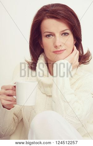 Vintage style portrait of beautiful happy mature woman with cup of tee in her hand