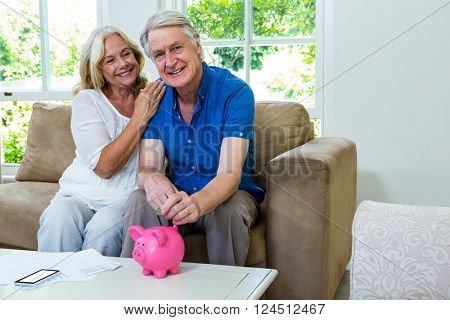 Smiling senior couple putting coin in piggi bank while sitting at home