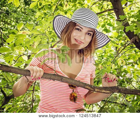 Young positive caucasian woman with stylish sunhat posing on the tree. Beauty and nature.