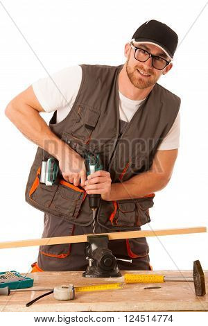 Young Carpenter Drilling A Hole In A Wooden Slat Isolated Over White Background