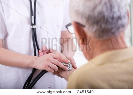 Close up of young nurse listening heartbeat with stethoscope on the old man's hand