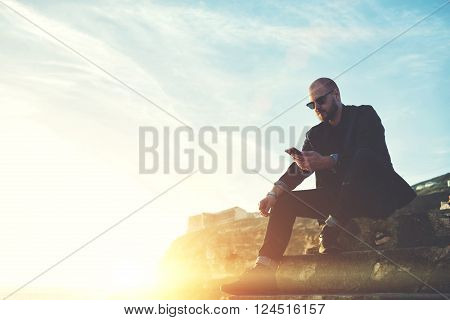 Confident man dressed in luxury clothes is reading text message on cell telephone while is sitting on stone rock against blue sky and sunset background with copy space for your content