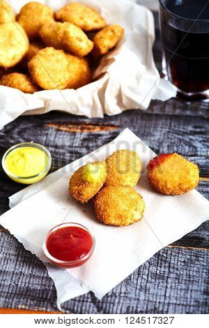 Crispy breaded golden chicken nuggets on parchment paper.  Ketchup and mustard near it. Textured wood background, Bowl with nuggets and glass of cola on backside
