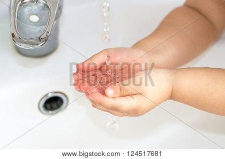 Clean Water From The Water Valve In Baby Child Palms