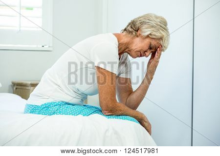 Tensed aged woman with eyes closed sitting on bed at home