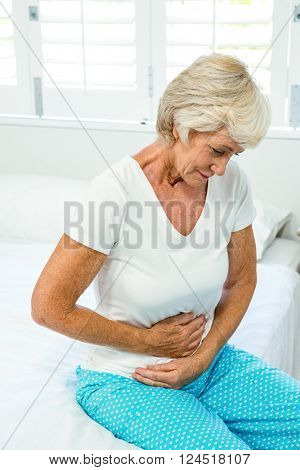 Senior woman suffering from stomach ache on bed at home