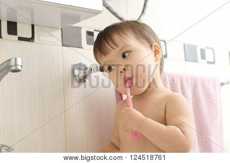 Caucasian baby child cleaning teeth in bathroom