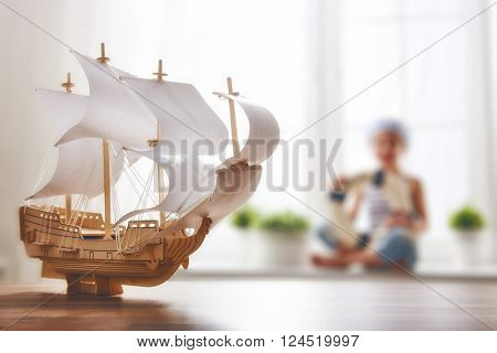 Child girl making model ship. Dreams of sea, adventures and travel.