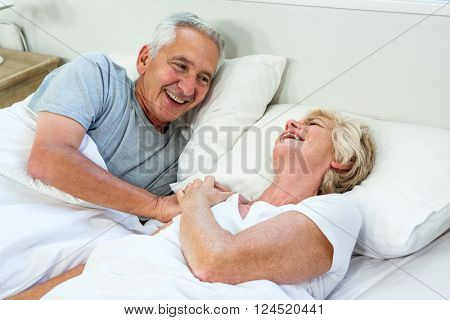 High angle view of smiling happy senior couple on bed at home