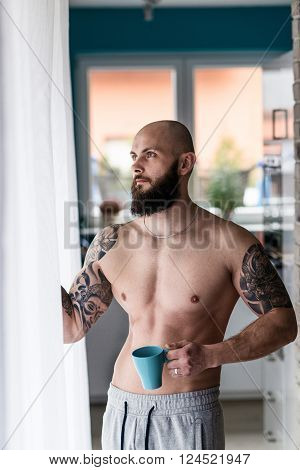 Muscular bearded man drinking coffee by the window. Lazy morning