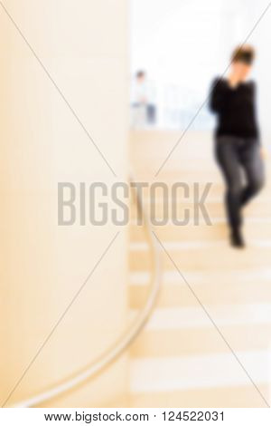 Woman in Museum climbing a flight of stairs man stands up defocused