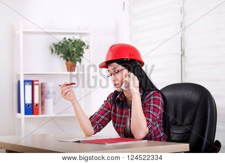 Woman Engineer Talking On The Phone In The Office