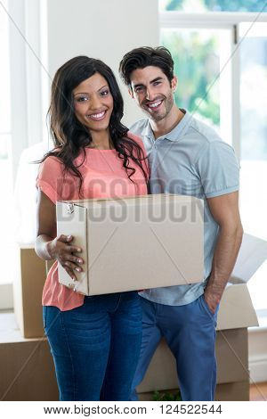 Portrait of young couple carrying cardboard box in their new house