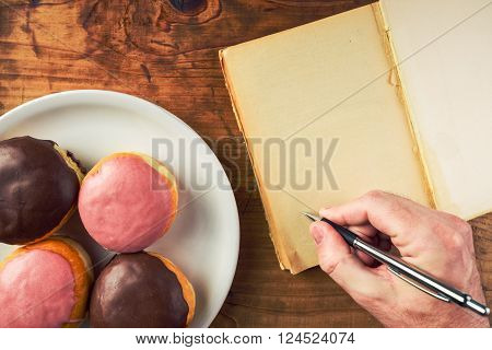 Writing recipe for homemade delicious doughnuts with sweet topping top view of male hand writing in notebook and tasty donuts with sweet strawberry and chocolate topping on a plate over polka dotted surface.
