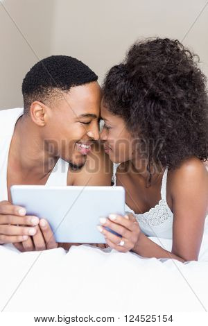 Young couple cuddling each other while holding digital tablet in bedroom