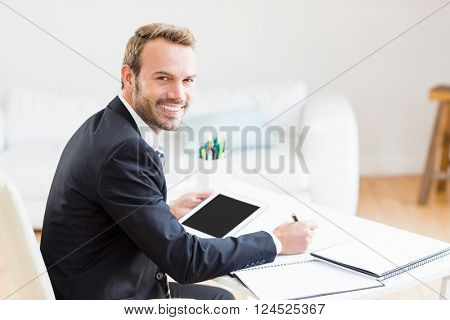 Portrait of businessman writing in a diary and using a digital tablet in office