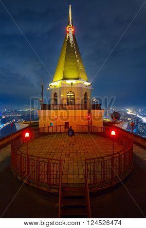 Man stands on circular observation deck with red lights on roof of tall building in night city