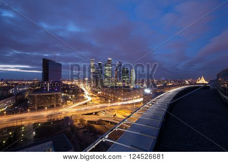 Highway, roof at night and modern skyscrapers in Moscow, Russia, long exposure