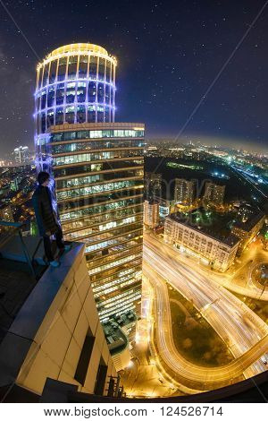 Man stands on roof of tall building in night with starry sky in city