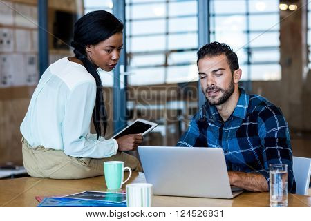 Young man and woman discuss using digital tablet and laptop in the office