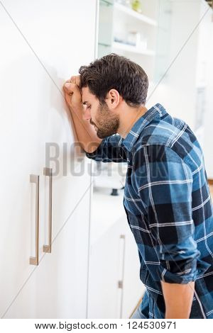 Depressed man leaning his head against a door at home