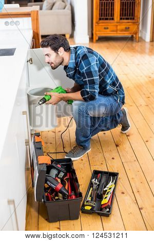 Man drilling a hole inside the cabinet at home