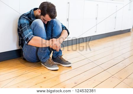 Tensed man sitting on wooden floor at home