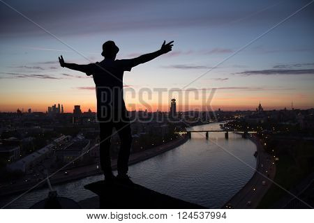 Silhouette of man posing on roof and Moskva river in evening in Moscow, Russia