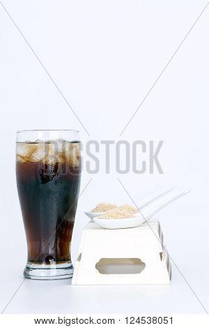 black drink (cola) and sugar over lettuce over white background