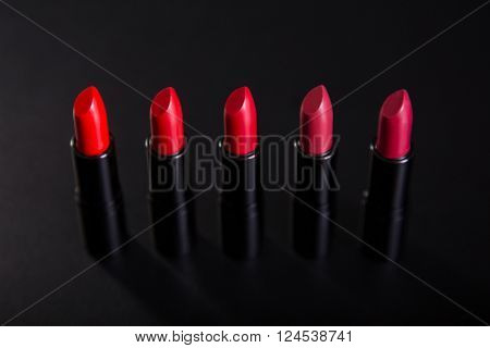 Row of bright red lipsticks, studio shot on black background